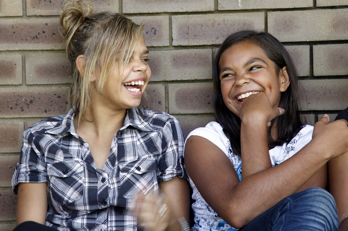 Two teenage Aboriginal girls laughing